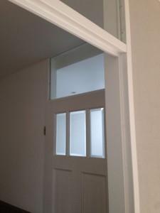 Afwerken en schilderen van deurkozijn en stucen van wanden en plafond